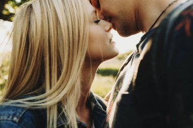 Crop close-up side view of attractive blond woman and handsome man kissing tenderly with closed eyes outdoors on backlit background