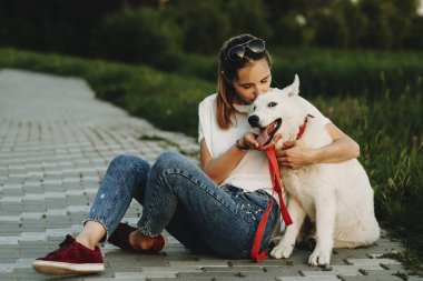 Woman in summer clothes sitting on pavement with crossed legs hugging and kissing happy white dog with open jaws looking at camera