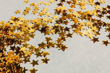 Closeup shot of golden star-shaped confetti spilled on light gray tabletop