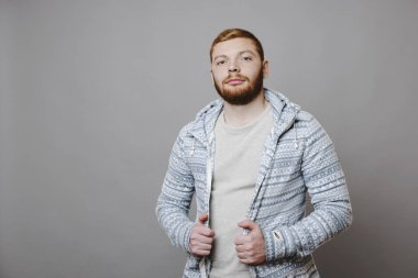 Attractive red-bearded male in patterned hoodie looking at camera with serious face expression while standing on gray background