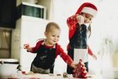 Fotografie Kleines Mädchen mit Baby Boy in Schürzen machen Cookies am Tisch und Spaß Mehl bestreuen