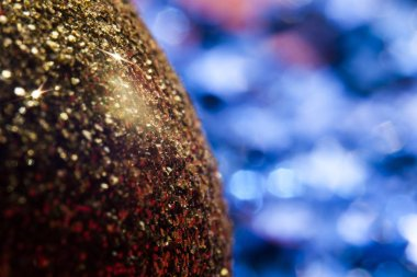 Closeup gold shiny bauble with smooth colourful spots of bright light shining on defocused background