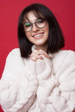 Delightful brunette woman with eyeglasses wearing a knitted white sweater is posing on a red studio wall with hands together smiling at camera