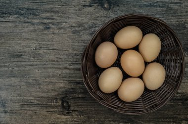 Chicken eggs in brown basket on brown wooden table background from top view.