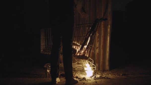 Bezdomovec a žena splnit krbu na dřevo v nákupním košíku a Begin oteplování navzájem ruce v pusté měst kolem v noci