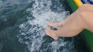 Young Woman Playing With The Surf With Her Feet, Dangling Her Legs From A Moving Fishing Boat Onto The Water Surface Of The Clear Tropical Sea.