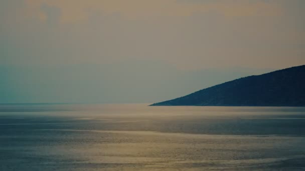Na středomořském pobřeží s tmavými kopci při západu slunce s mraky v noci padá čas..
