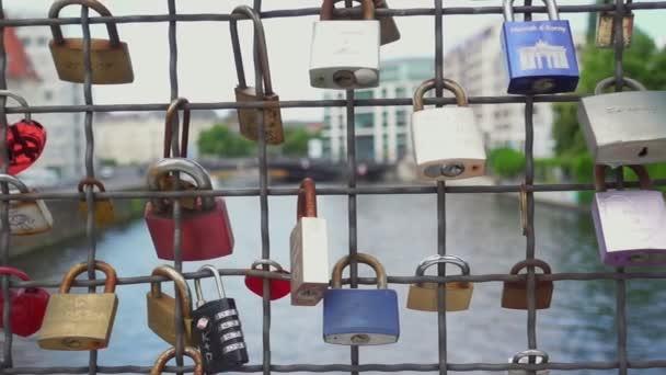 Pomalý pohyb, snímek mnohých uzamykacích skřínků v různých barvách visícími na mostě přes řeku Spree v Berlíně.