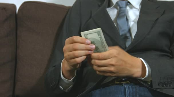 Businessman counting money and puts them in his pocket