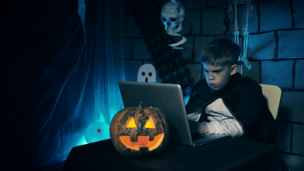 Young boy in a vampire costume for Halloween showing his scary face and teeth to people over internet