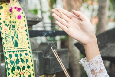 hands of balinese woman doing ritual praying with canang sari