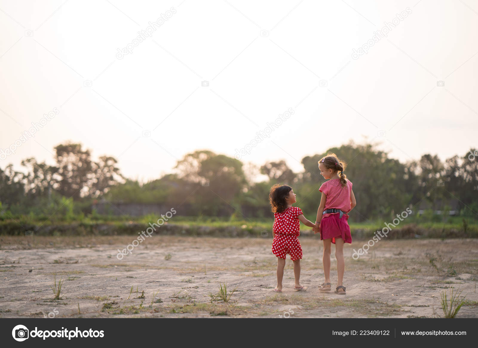 bc671d33db Two young children holding hand while walking in the field. shoot from  behind — Photo by odua