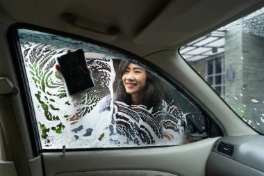 woman wash her car window with soap