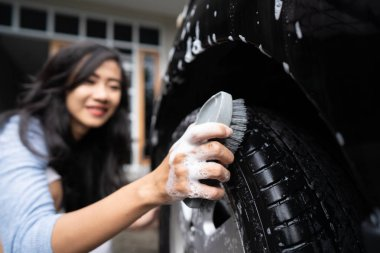 attractive young woman cleaning up her car with water and soap at home by herself