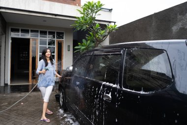woman cleaning and washing her black car