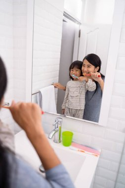 mother and daughter brushing teeth in the bathroom sink