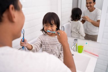 kid and dad having fun while brushing their teeth