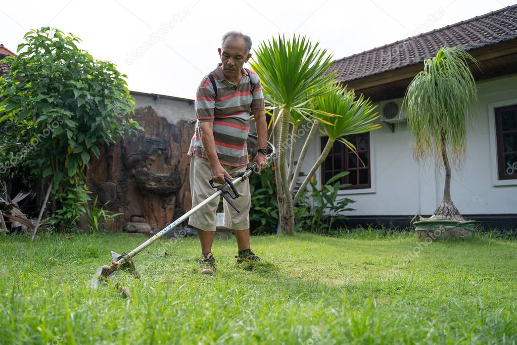old asian man mowing his garden