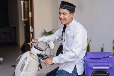 muslim man ride motorcycle for idul fitri balik kampung mudik carrying suitcase