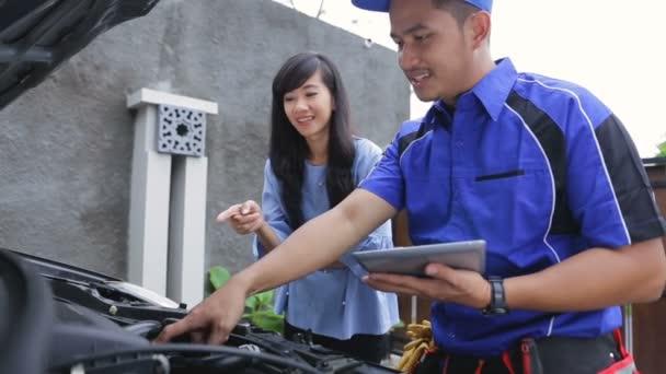 Techniker helfen dem Kunden beim Reparieren seines Autos