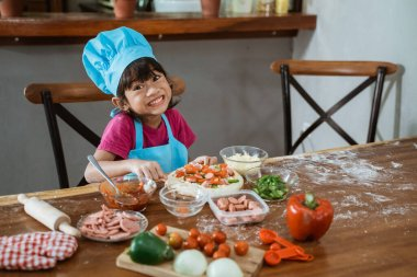 Little girl in a blue apron making pizza crust for delicious homemade pizza