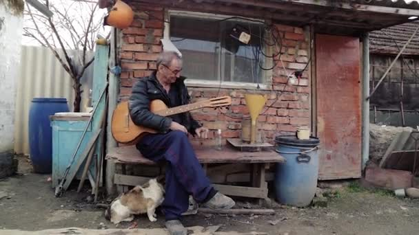 Russian old man in dirty clothes and a guitar drinking vodka, sitting in the yard in the village. Drinking man. National Russian man drinking and playing guitar