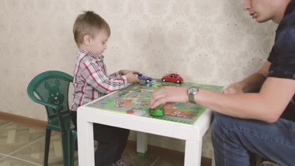 Father and son are playing with toy cars and smiling while spending time together at home