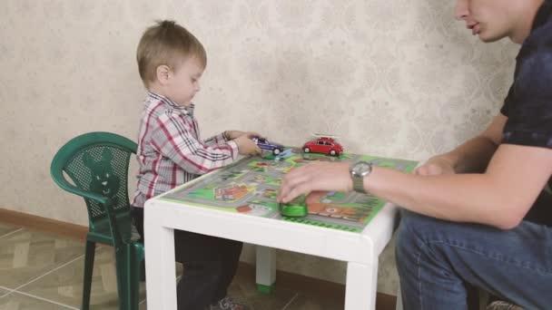 Padre e figlio sono giocare con le macchinine e sorride mentre trascorrere del tempo insieme a casa