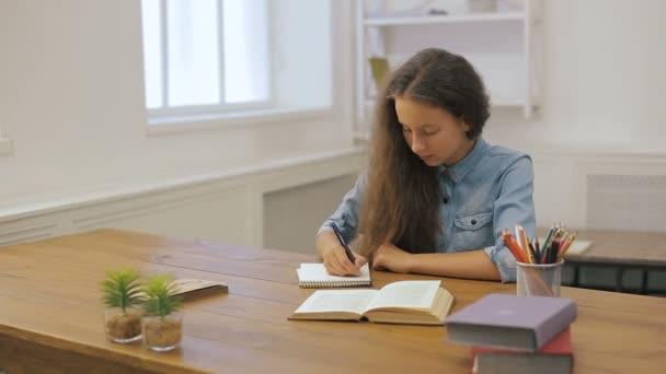 Mladá dívka s přenosným počítačem dělá domácí práce. Vysokoškolské vzdělání. Studentka studuje doma.