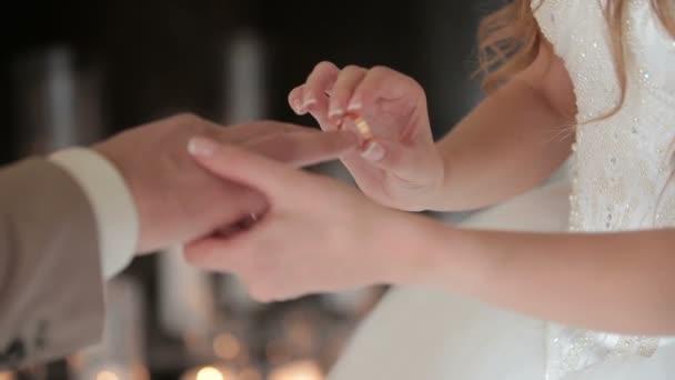 Bride wears ring on grooms finger. The bride and groom exchange wedding rings.