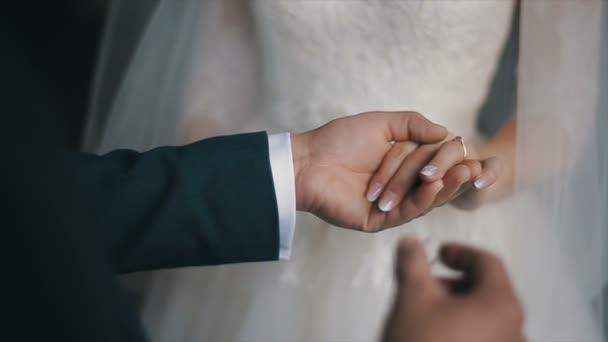 A vőlegény hozza a wedding ring ujját a menyasszony. házasság kéz gyűrűs. A menyasszony és a vőlegény cseréje esküvői Jegygyűrűk.