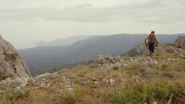 Jistý muž s batohem je Turistika v horách. Sport, fitness a zdravého životního stylu venku v létě příroda