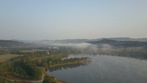 Filmový letecký pohled na ranní mlhy nad horským jezerem. Mlhavé svítání v horách