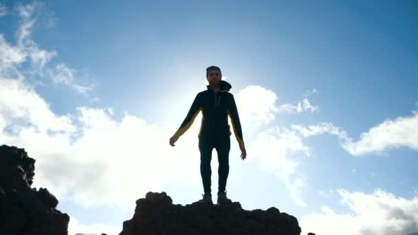Mann springt in Zeitlupe gegen schönen Himmel. Sonnenlicht.