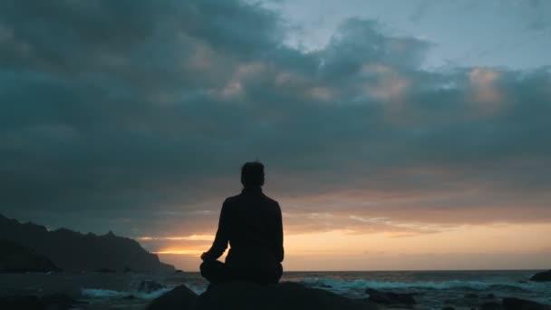 Silhouette einer Frau, die bei Sonnenuntergang auf Felsen sitzt und Meereswellen am Strand von Benijo auf Teneriffa beobachtet, Kanarische Inseln.