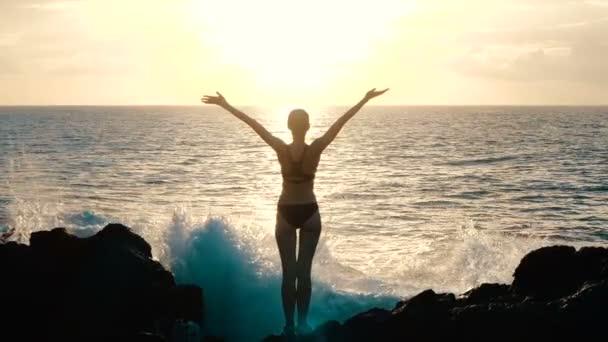 Sziluettje egy nő a naplemente fegyvert a levegőben, és megfigyelő hatalmas óceán hullámai összeomlik a sziklák és a permetezést. Filmszerű lassú mozgás