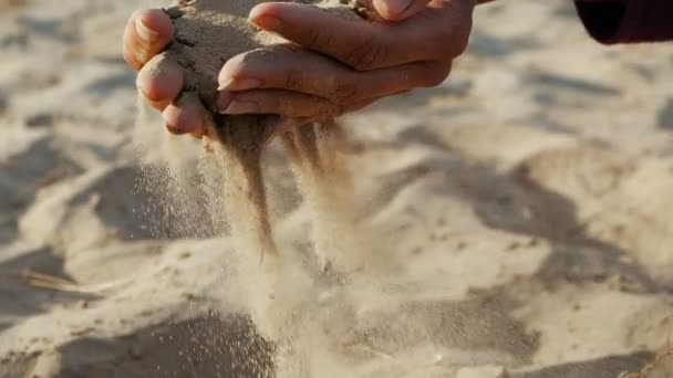 SLOW MOTION, CLOSE UP: The sand passes through the fingers of a young woman. The sand is running through fingers of a lady and is spread by a strong wind.