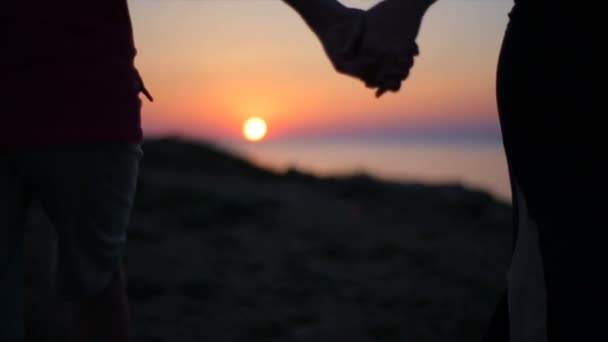 Clode-up of a Young couple in love holding hands walking against beautiful sunset over a sea.