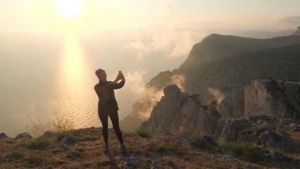 Krásná žena, která má videokonverzaci pomocí smartphone venku proti nádhernému dramatickému západu slunce nad mořem z vysoké hory na Krymu. Dívka filmovat video mobilní telefon užívající dovolenou
