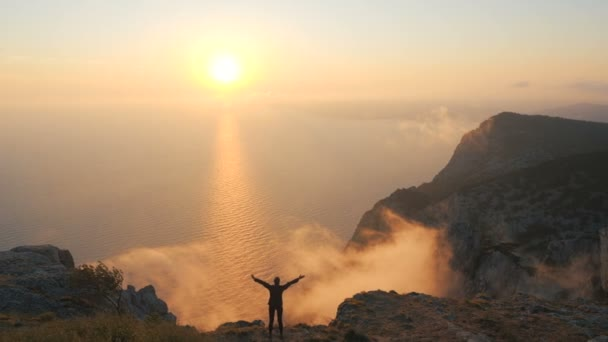 Silhuette Young Woman arms outstretched observing a beautiful dramatic sunset above a sea from the top of a high mountain in Crimea.