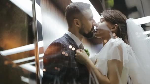 Ženich a nevěsta se líbají ve výtahu. Novomanželé se objímají, dívka táhne chlapa za bundu pro sebe. Svatební milostné video.