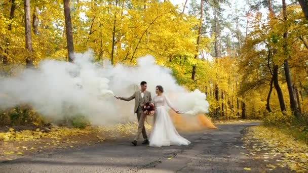 Slow motion. Young attractive Bride and Groom hold burning smoke bombs and walk along a road in autumn forest. Happy loving newlyweds among Colored fall trees in a park.