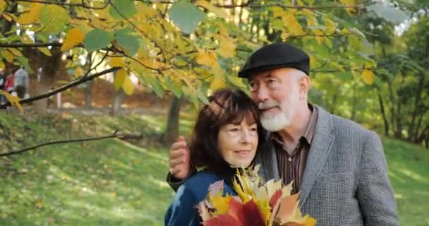Happy senior husband and wife hugging under a tree branch, enjoy a warm, sunny autumn in a cozy park - slow motion. Woman holds a bouquet of leaves.