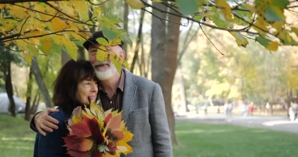 Happy elderly couple in hugs enjoys autumn in a cozy park among the trees - slow motion.