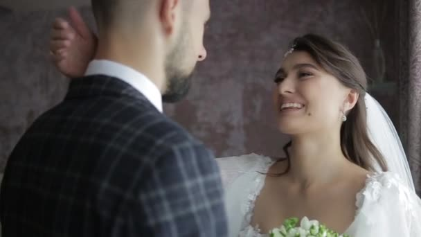 Close-up shot of beautiful bride with diadem on her head, with bouquet of flowers and in a chic white wedding dress kissing her beloved groom in a plaid suit in the morning in an expensive hotel room