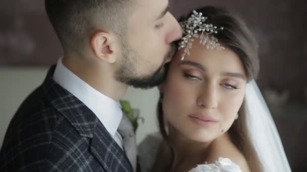 Happy morning for young millennial wedding couple hugging and kissing in the bedroom in the morning, close view. Bearded groom kisses the bride in beautiful white wedding dress and wreath on head.