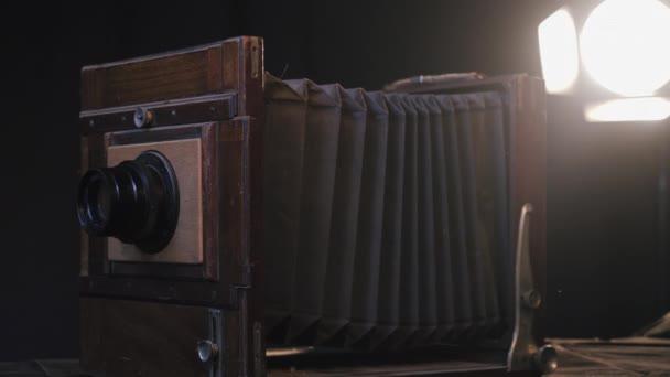 Közelkép a vintage fa retro fényképezőgép az asztalon elszigetelt sötét stúdió szobában, háttérvilágító lámpa. Antik elavult, ritka régi stílusú fényképészeti berendezések restaurálása, javítása.