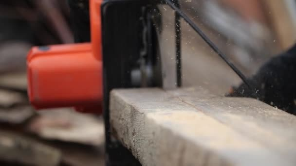 Běžící kruhový stroj na tlusté desce v rozmazaném pozadí, se zaměřením na kus dřeva a létající piliny ve vzduchu, detailní záběr ve zpomaleném filmu. Tesař pilky a řezné brusky na dřevěné desce.