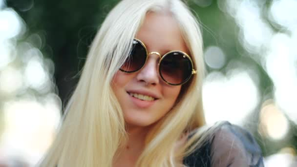 A feminine teenager in round sunglasses in a gold rim, which reflects the sun and the park, smiles cheerfully, showing his even white teeth. A girl with long blond hair is resting in nature.