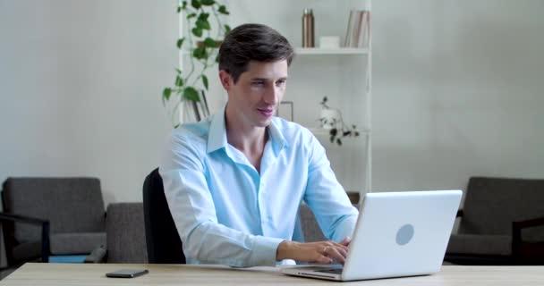 Portrét úspěšného tisíciletého obchodníka, který pracuje na laptopu, on-line obchod na internetu, dívá se na kameru ukazující palce nahoru, dává vysoké známky, znamení souhlasu, symbol podpory spokojenosti